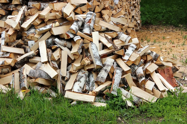 Pile of logs on the grass, chopped by an axe Premium Photo