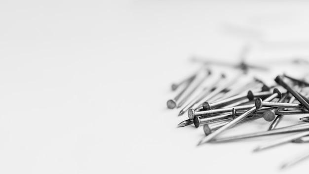 Pile of metallic nails on white table Free Photo