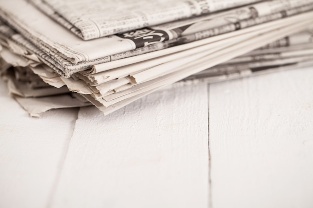 Pile of newspapers on a white table Free Photo