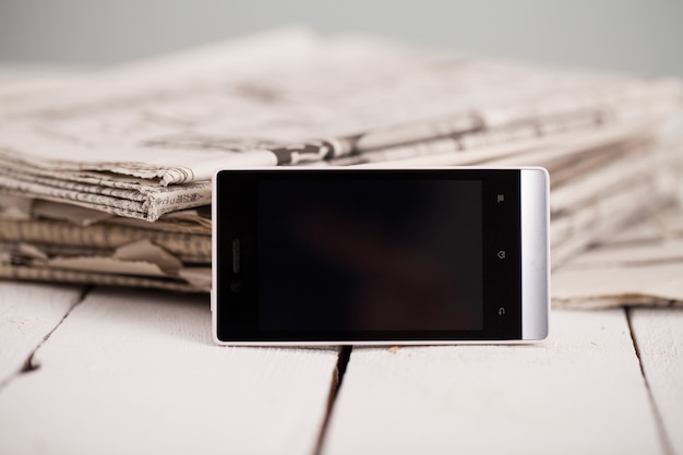 Pile of newspapers with smartphone on it Free Photo