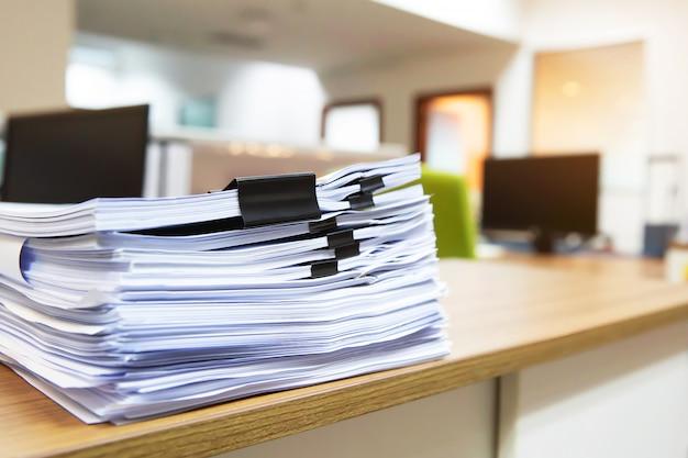 Куча много бумаг на стол офиса складывают. Premium Фотографии