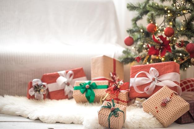 Куча рождественских подарков над светлой стеной на деревянном столе с уютным ковриком. рождественские украшения Бесплатные Фотографии