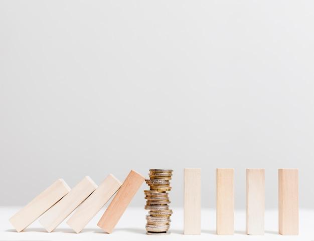 Куча монет, останавливая упавшие деревянные части вид спереди Premium Фотографии