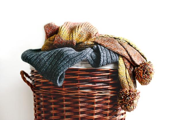 分離されたわらのバスケットにニットの冬のスカーフの山 Premium写真