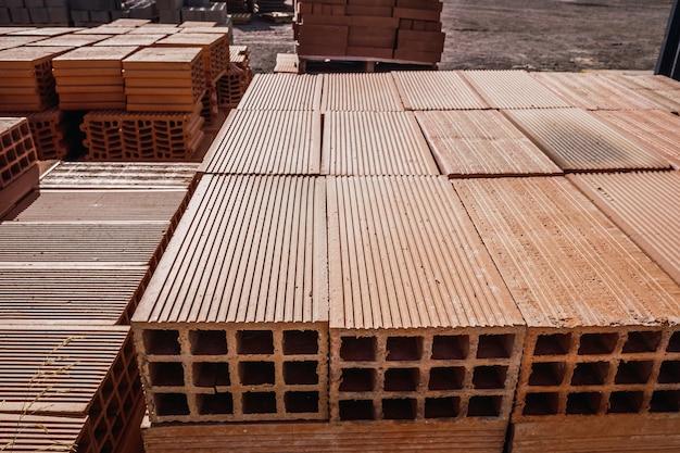 建物の供給店で壁を構築するために積み重ねられた新しいレンガの山。 Premium写真