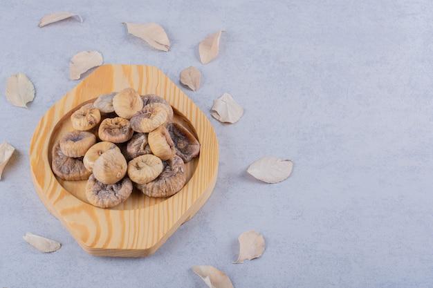 Куча сладкого сушеного инжира на деревянной тарелке с листьями. Бесплатные Фотографии