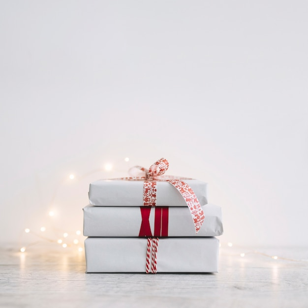 Pile of white gift boxes with garland on table Free Photo