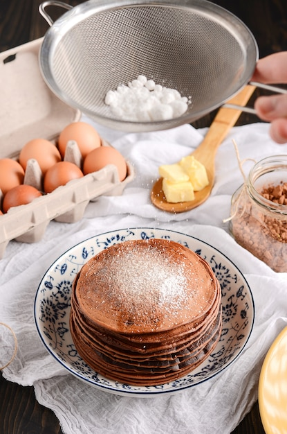 A pile of pancakes with a wooden spoon of butter, eggs, on a rustic wooden table. Premium Photo