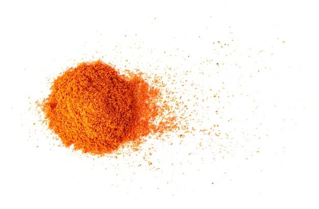 Pile of red paprika powder on white wall. Premium Photo