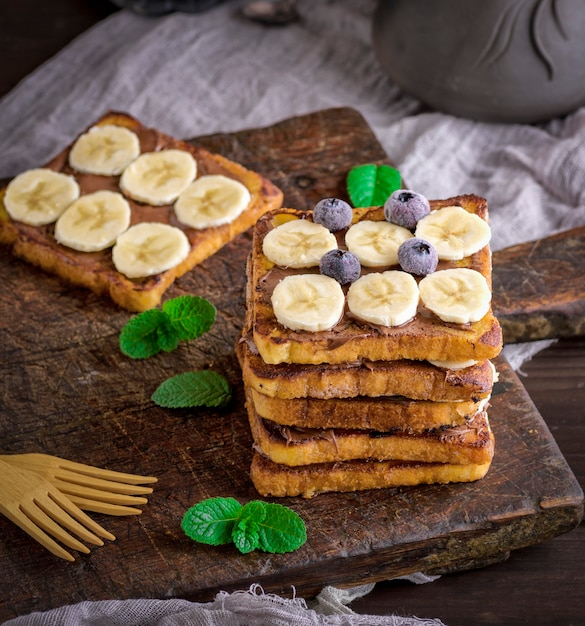 Pile of square fried bread slices with chocolate and banana Premium Photo