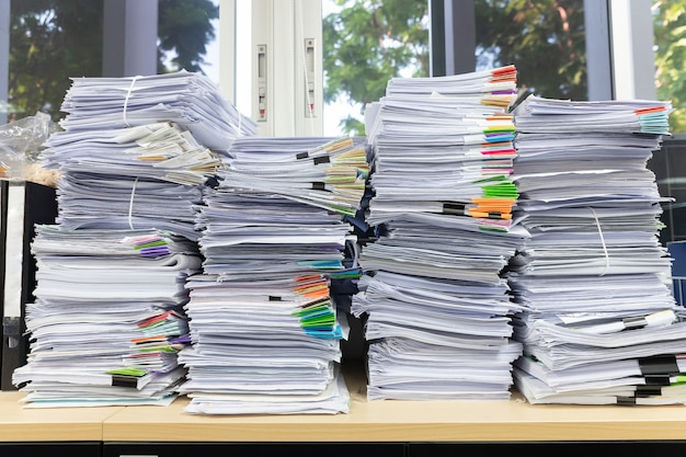 Pile of unfinished documents on office desk Premium Photo