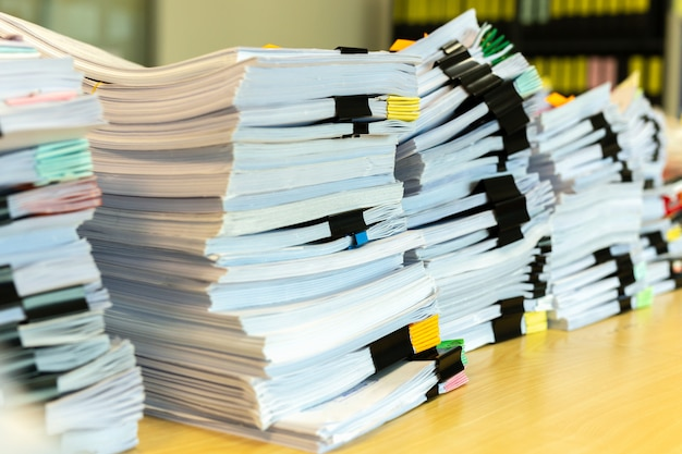Pile of unfinished documents on office desk. Premium Photo