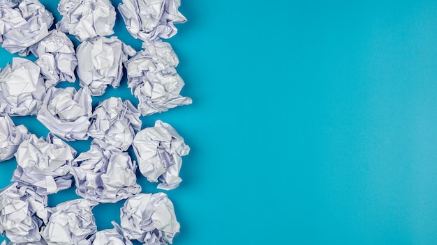 Pile of a white crumpled paper balls on blue background. Premium Photo