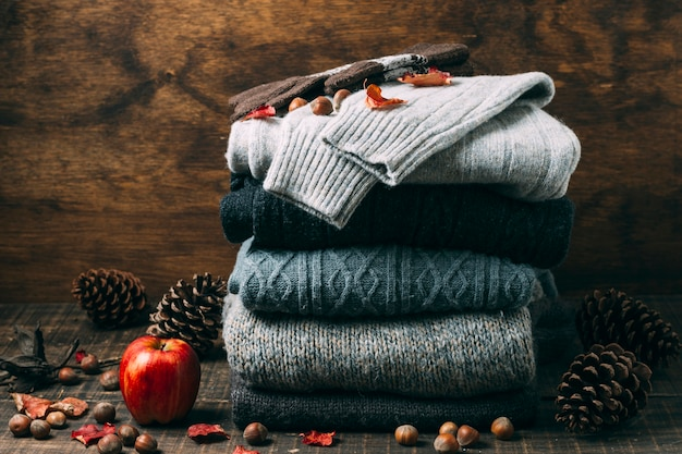 Pile of winter sweaters with an apple Free Photo