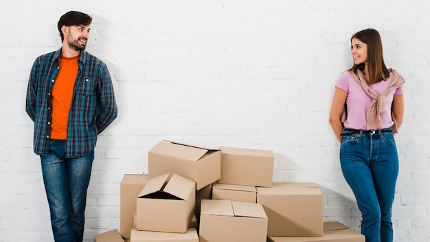 Piles of cardboard boxes between the stylish young couple standing against wall looking to camera Free Photo