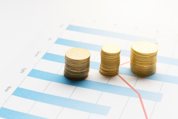Piles of coins on top of graph Free Photo