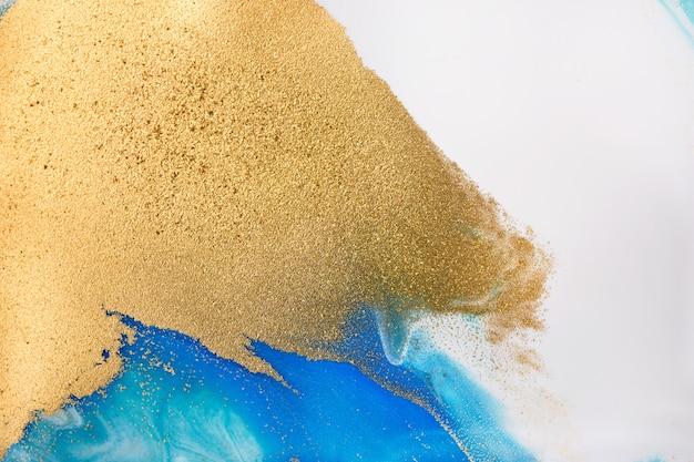 Груды золотых блесток на синих пятнах краски Premium Фотографии