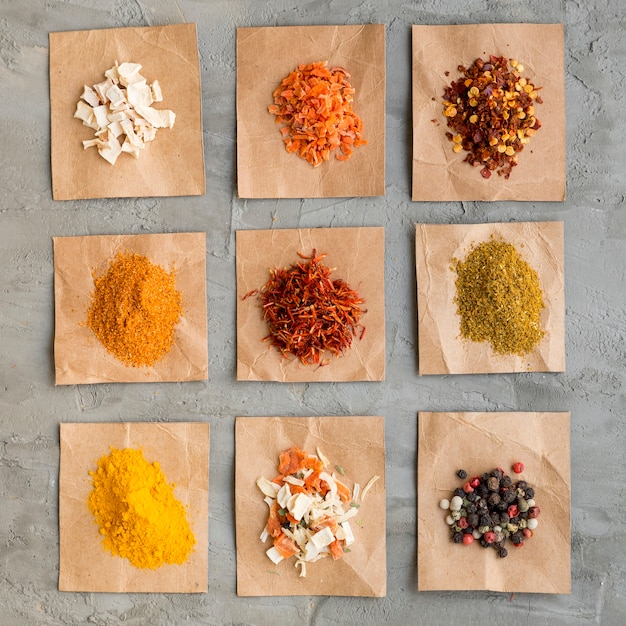 Piles of spices on pieces of paper Free Photo