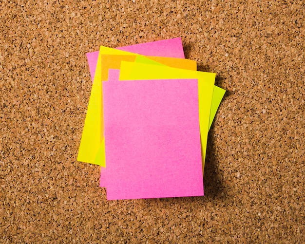 Piles of stick notes on cork board Free Photo