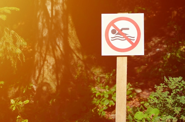 A pillar with a sign denoting a ban on swimming. the sign shows a crossed-out floating person Premium Photo