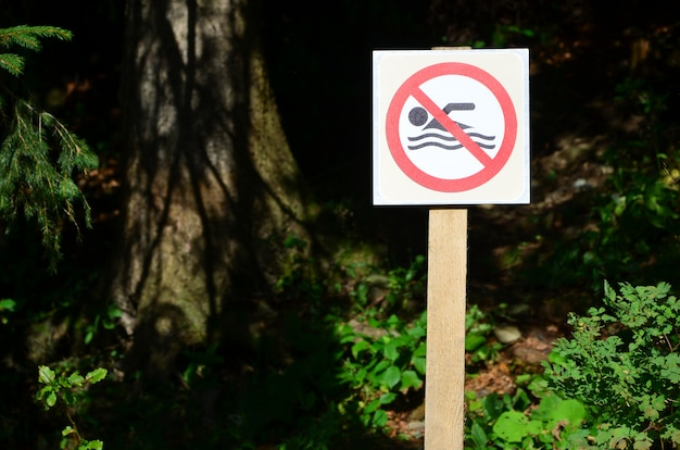 A pillar with a sign denoting a ban on swimming. Premium Photo