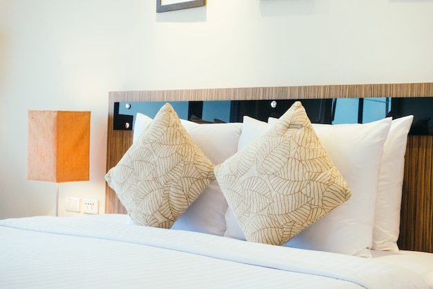 Pillow on bed with light lamp Free Photo