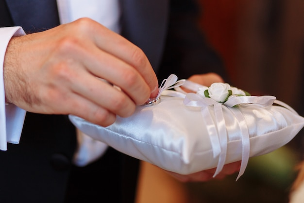 Pillow with wedding rings. groom taking ring during ceremony Free Photo