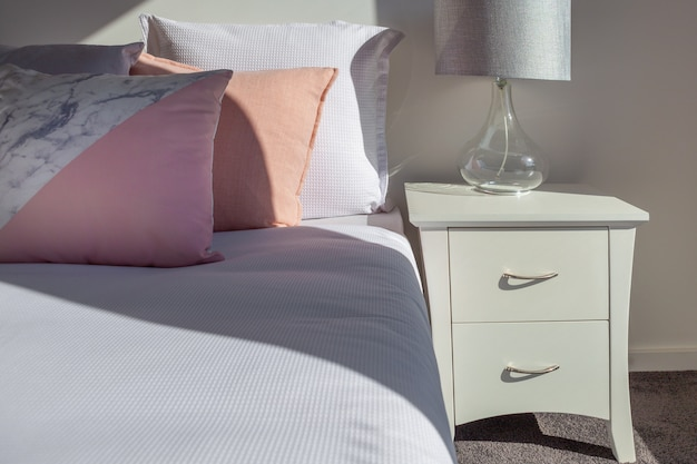 Pillows on bed with white bedside table and bedroom lamp close-up Premium Photo