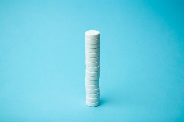 Фон таблетки. таблетки, лекарства и концепция медицины. белые таблетки на синем фоне Premium Фотографии