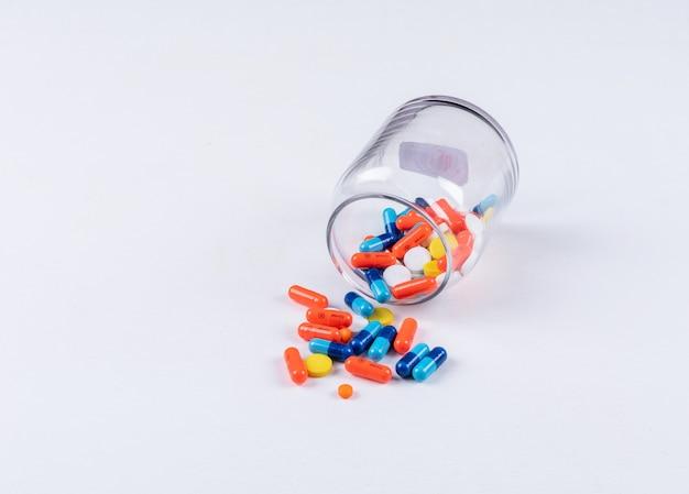 Pillole che escono dal barattolo Foto Gratuite