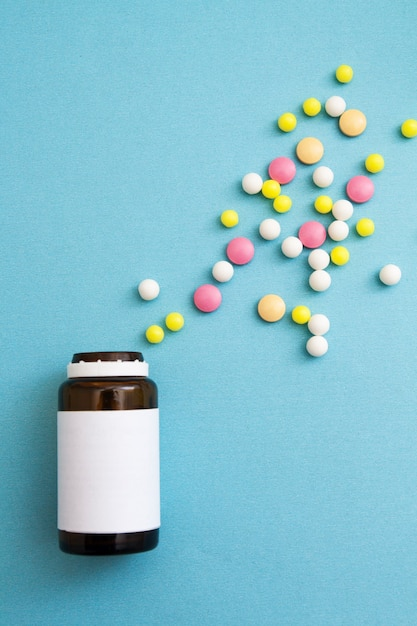 Pills of different colors and shapes next to a bottle on a blue background. medical concept, treatment, health. pill bottle mockup Premium Photo