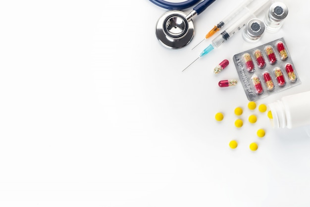 Pills spilling out of pill bottle syringe thermometer and stethoscope on white background Premium Photo