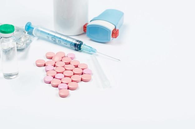 Таблетки, шприц, перчатки на белом столе Premium Фотографии