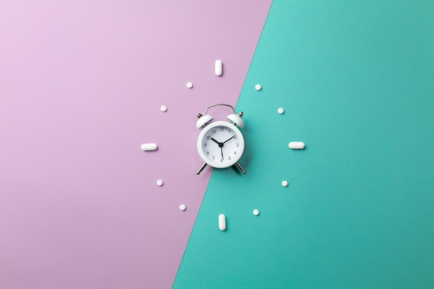 Pills, tablets and white alarm clock on on green and purple Premium Photo