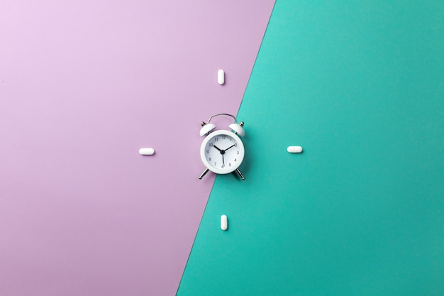 Pills, tablets and white alarm clock on green and purple Premium Photo