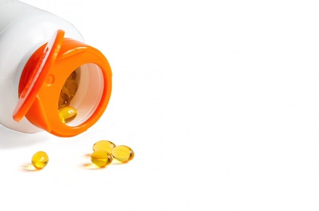 Pills of vitamin d3 and bottle with open cap Premium Photo