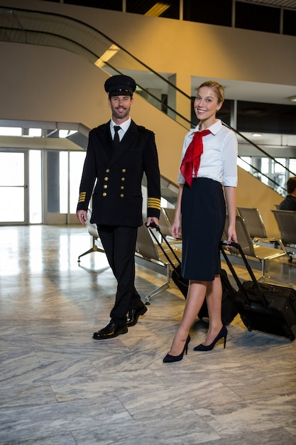 Pilot and air hostess walking with their trolley bags Free Photo