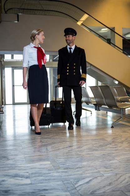 Пилот и стюардесса идут с сумками на колесиках Бесплатные Фотографии