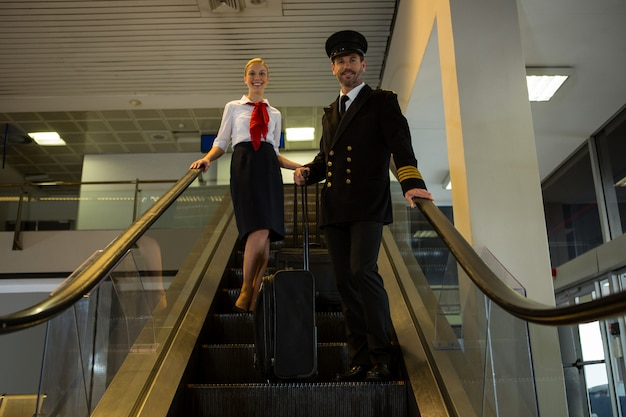 Пилот и стюардесса с сумками на тележке, стоящими на эскалаторе Бесплатные Фотографии