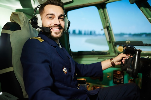 Pilot posing in plane  cabin Premium Photo