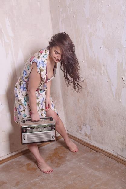 Приколите фото старомодной молодой женщины со старым радио Premium Фотографии