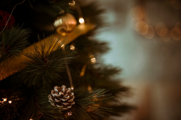 Pine cone on christmas tree decorated with wreath and balls Free Photo