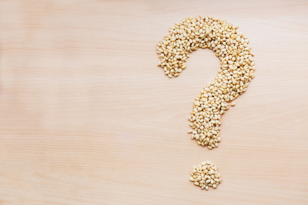 Pine nuts in the shape of question mark on light wooden background. template of nuts on the table Premium Photo