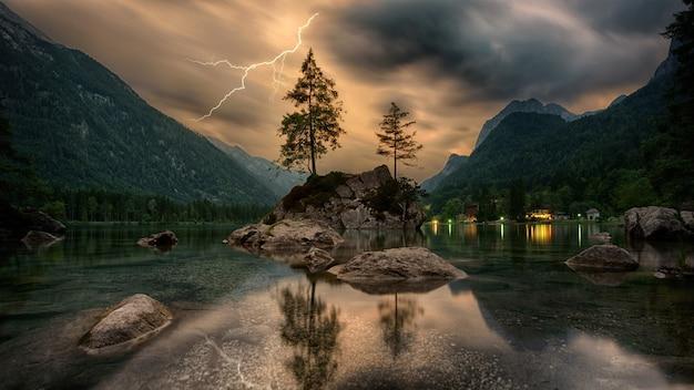 灰色の雲の下の山の近くの岩層の松の木 無料写真