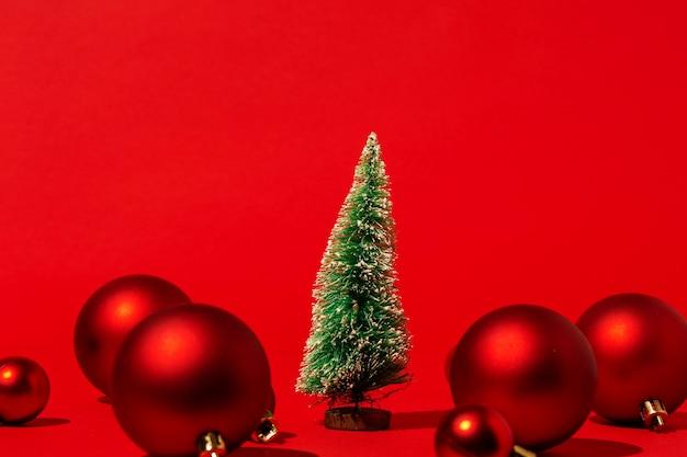붉은 벽에 빨간색 크리스마스 볼 소나무 무료 사진