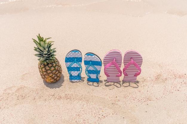 Ананас и тапочки на тропическом пляже Premium Фотографии