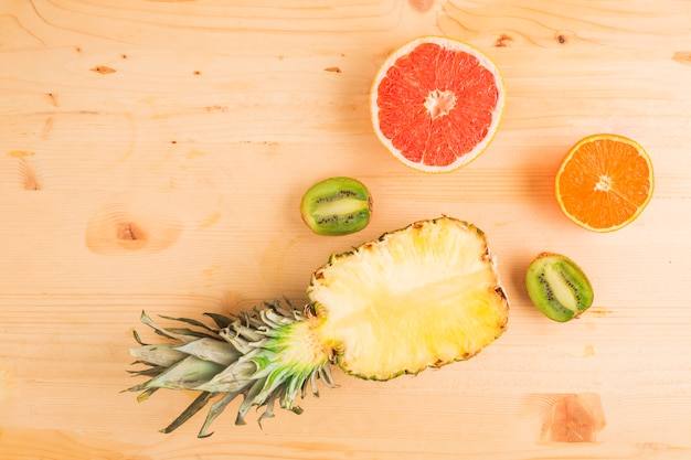 Pineapple and citrus fruits on wooden table Free Photo