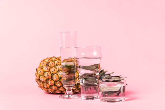 Pineapple behind containers of water Free Photo