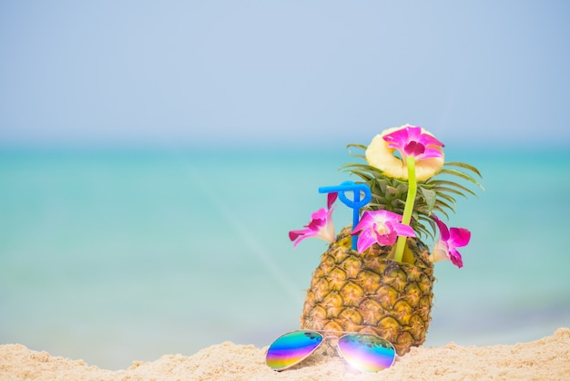Pineapple fruit on beach with blue sea background, summer fruit drink concept. Premium Photo