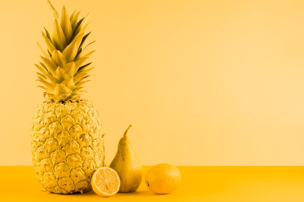 Pineapple; pear and halved lemon on yellow background Free Photo